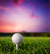 Golf Course Posters - Golf ball on tee at sunset Poster by Michal Bednarek