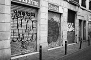 Grafitti Photos - grafitti on shutters of closed shops in downtown old town Barcelona Catalonia Spain by Joe Fox