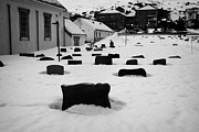 Snow Drifts Prints - gravestones partially buried in the snow in the cemetery outside Honningsvag kirke church finnmark  Print by Joe Fox