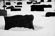 Snow Drifts Prints - gravestones partially buried in the snow in the cemetery outside Honningsvag kirke church Print by Joe Fox