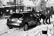 Helping Prints - group of men pushing car stuck in deep snow on downtown city street Saskatoon Saskatchewan Canada Print by Joe Fox