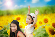 Enjoying Prints - Happy family with beautiful sunflowers Print by Anek Suwannaphoom