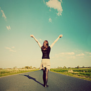 Victory Field Photo Prints - Happy woman standing on empty road Retro vintage style Print by Michal Bednarek