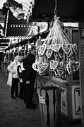 Berlin Germany Framed Prints - heart shaped Lebkuchen hanging on a christmas market stall with tourists browsing in Berlin Germany Framed Print by Joe Fox