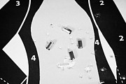 Round Shell Photo Prints - Human Shaped Target Ridden With Bullet Holes And 9mm Empty Shell Casings Print by Joe Fox