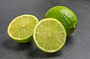 Cut In Half Photos - Limes on a slate plate by Palatia Photo