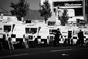 Violent Prints - Line of PSNI landrovers and officers on crumlin road at ardoyne shops belfast 12th July Print by Joe Fox