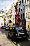 Townhouses Posters - London taxi on shopping street Poster by Elena Elisseeva
