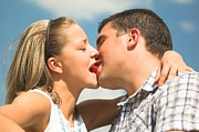 Women Together Posters - Lovely couple kiss-eating a strawberry Poster by Michal Bednarek