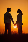 Woman In Summer Meadow Posters - Lovers Holding Hands At Sunset In Silhouette Poster by Lee Avison