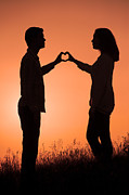 Woman In Summer Meadow Posters - Lovers Making A Heart Shape At Sunset Poster by Lee Avison