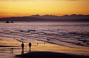 Alki Beach Framed Prints - Low tide at Alki in West Seattle at sunset with silhouetted peop Framed Print by Jim Corwin