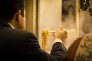 Noodles Prints - Man eating noodles in a restaurant Print by Ruben Vicente