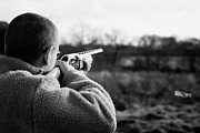 Target Field Prints - Man In Fleece Jacket Firing Shotgun Into Field With Cartridge Ejecting On December Shooting Day Print by Joe Fox