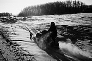Harsh Conditions Prints - man on snowmobile crossing frozen fields in rural Forget canada Print by Joe Fox