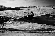 Harsh Conditions Art - man on snowmobile crossing frozen fields in rural Forget Saskatchewan Canada by Joe Fox