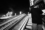 Escalator Prints - man riding on escalators on Las Vegas boulevard Nevada USA Print by Joe Fox