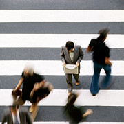 Crosswalk Prints - Man walking and reading newspaper on zebra crossing Print by Juan Carlos Ferro Duque