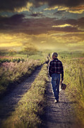 Sandra Cunningham - Man walking down a country road at sunset
