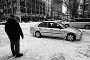 Crosswalk Prints - man watching car travelling along snow covered city streets in Saskatoon Saskatchewan Canada Print by Joe Fox