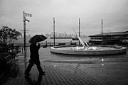 North Vancouver Framed Prints - man with umbrella walking towards seabus terminal in the rain north Vancouver BC Canada Framed Print by Joe Fox