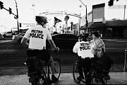 Policewoman Framed Prints - metro police bicycle cops help a tourist with directions in downtown Las Vegas Nevada USA Framed Print by Joe Fox