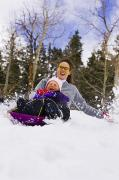 Enjoying Prints - Mother & Daughter Sledding Together Print by Michael DeYoung