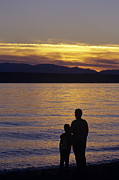 Tender Moment Framed Prints - Mother and daughter holding each other along Edmonds Beach at su Framed Print by Jim Corwin