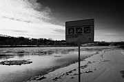 Sask Prints - no swimming sign at the south saskatchewan river in winter flowing through downtown Saskatoon Saskat Print by Joe Fox