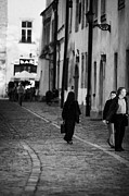 Old Krakow Framed Prints - nun with briefcase walking up cobblestone street Kanonicza past tourists in old town krakow Framed Print by Joe Fox