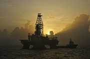Sea Platform Posters - Offshore Oil Rig With Sun And Clouds Poster by Bradford Martin