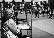 Old Krakow Framed Prints - Old Female Street Vendor Selling Bread Looks Out To Crowd In Rynek Glowny Town Square Krakow Framed Print by Joe Fox
