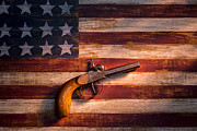 Low Key Photo Prints - Old gun on folk art flag Print by Garry Gay