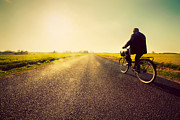 Road Travel Posters - Old man riding a bike to sunny sunset sky Poster by Michal Bednarek