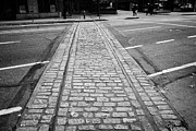 Tram Prints - old streetcar rails and cobbles in west pender st at international village Vancouver BC Canada Print by Joe Fox