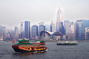 Ferry Photos - Old traditional chinese junk in front of Hong Kong Skyline by Lars Ruecker