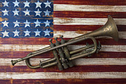 Wind Photos - Old trumpet on American flag by Garry Gay