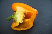 Dark Gray Framed Prints - Orange bell pepper cut in half Framed Print by Matthias Hauser