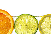 Green. Orange Posters - Orange lemon and lime slices in water Poster by Elena Elisseeva