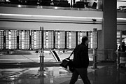 Air Travel Framed Prints - passenger walking past departures board at Denver International Airport Colorado USA Framed Print by Joe Fox