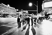 Crosswalk Posters - People Waiting To Cross Las Vegas Boulevard Outside The Bellagio And Paris At Night Nevada Usa Poster by Joe Fox