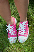 Trendy Art - Pink sneakers on girl legs on grass by Michal Bednarek