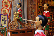 Toy Shop Prints - Pinocchio inviting tourists in souvenirs shop Print by Kiril Stanchev