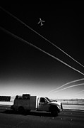 Air Travel Framed Prints - Plane Taking Off Into Blue Sky With Contrails At The End Of The Runway Over Passing Truck At Mccarra Framed Print by Joe Fox