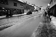 Flooding Photos - pools of thawing water from ice on main shopping street storgata Honningsvag finnmark norway europe by Joe Fox
