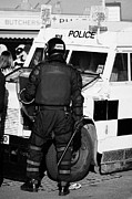 County Police Posters - PSNI officer with riot gear and baton in front of land rover on crumlin road at ardoyne shops belfas Poster by Joe Fox