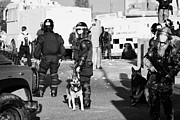 County Police Posters - PSNI riot officers and dog handler and armed soldiers on crumlin road at ardoyne shops belfast 12th  Poster by Joe Fox