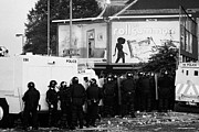 Unrest Framed Prints - PSNI riot officers behind armoured land rover water cannon beneath on crumlin road at ardoyne shops  Framed Print by Joe Fox