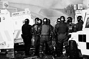 County Police Posters - PSNI riot officers watch rioting and water canon on crumlin road at ardoyne shops belfast 12th July Poster by Joe Fox