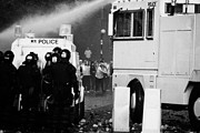 Rover Posters - PSNI riot police behind armoured land rover and water canon face on crumlin road at ardoyne Poster by Joe Fox